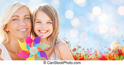 happy mother and little girl with pinwheel toy - summer ...