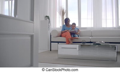 Happy mother and little son reading a book in the morning...
