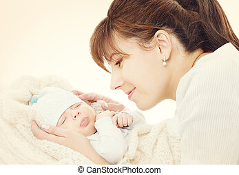 Happy Mother and Sleeping Newborn Baby, mom looking to New Born Kid, Family portrait