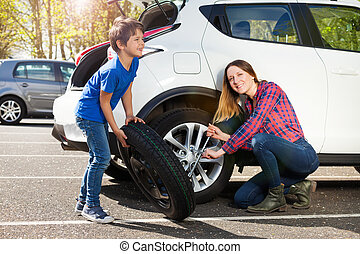 Happy mother and son changing flat tire together - Portrait ...