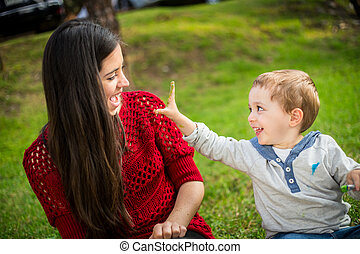 Happy Mother and son child playing in the park