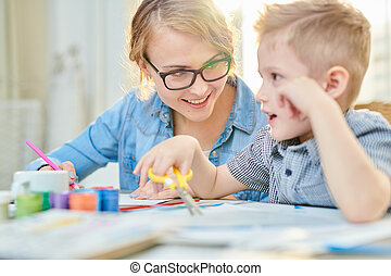 Happy Mother and Son Crafting Together in Sunlight