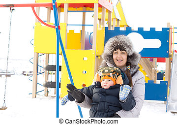 Happy mother and son in winter outfits waving
