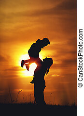 Happy mother and son playing against setting sun - Happy...