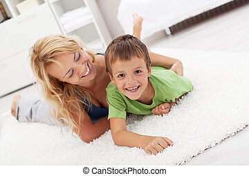 Happy mother and son playing in the living room wrestling on...