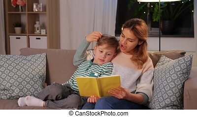 happy mother and son reading book sofa at home - family, ...