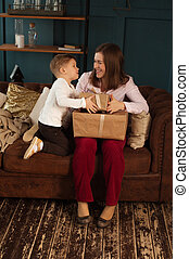 Happy mother and son sitting with giftboxes