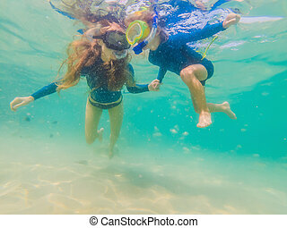 happy mother and son snorkeling in the sea. Look at the fish under water