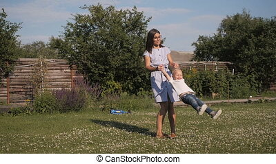 Happy Mother And Son Spinning In The Garden. Mom and Son Having Fun