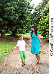 mother and son walking in fruit orchard