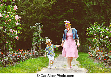 Happy Mother and son walking in summer park with flowers. Warm toned image