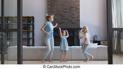 Happy mother and two daughters dancing together in living room