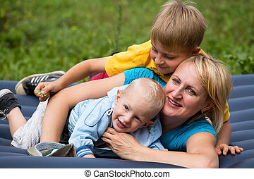 Happy mother and two sons in the park