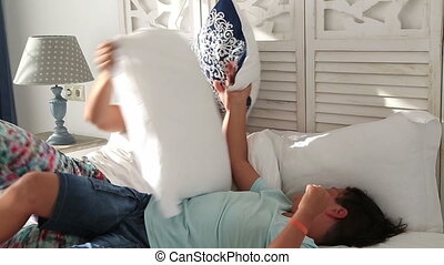 Happy mother ans son having pillow fight