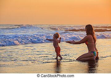 Happy mother, baby son has fun in sea beach surf