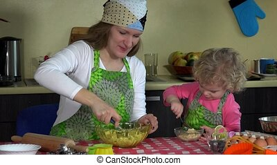 happy mother baking with little daughter in apron. family girls in kitchen
