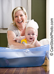 Happy mother bathing cute baby