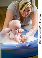 Happy mother bathing her cute baby