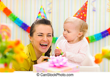 Happy mother celebrating first birthday of her baby