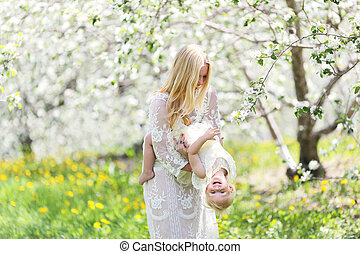 Happy Mother Dancing with Baby Daughter in Flowering Apple Orchard