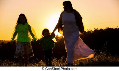 Happy Mother Dancing With Son And Daughter At Sunset