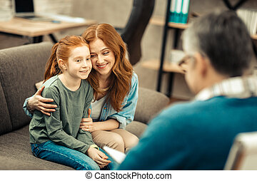 Delighted positive woman smiling to her daughter