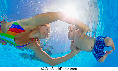 Happy mother dive underwater with little child in swimming...