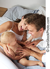 Happy mother father and baby laughing together