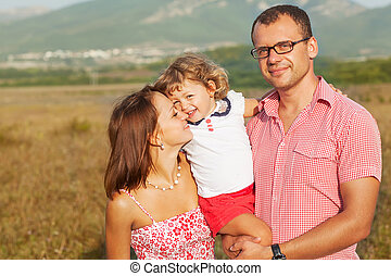 Happy mother, father and daughter in the mountains at sunset