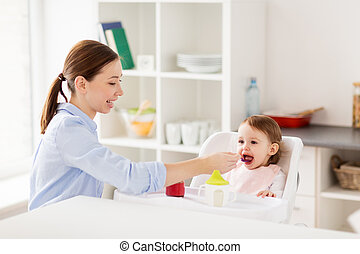 happy mother feeding baby with puree at home - family, food,...