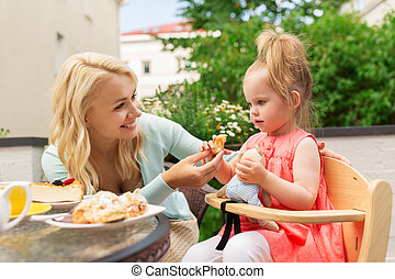 happy mother feeding daughter with cake at cafe