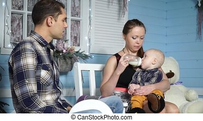 Mother feeds baby from a bottle while sitting on a bench next to his father