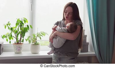 Happy mother gently kisses and strokes her baby in a room by...