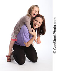 Happy mother giving daughter fun piggy back ride
