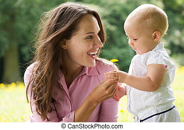 Happy mother giving flower to baby in the park