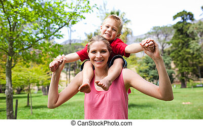 Happy mother giving her son a piggyback ride