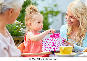 happy mother giving present to daughter at cafe