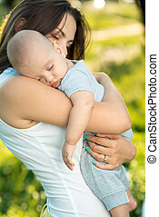 Happy mother holding a young sleeping son in the park