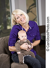 Happy mother holding baby on couch at home