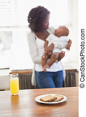 Happy mother holding baby son at breakfast time