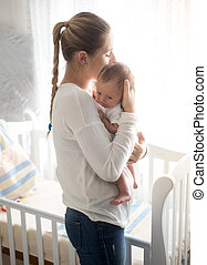 Happy mother holding her baby at bedroom