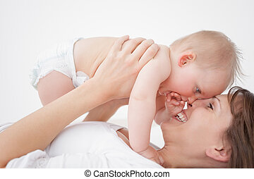 Happy mother holding her daughter while lying