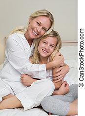 Happy mother hugging cute daughter in bed