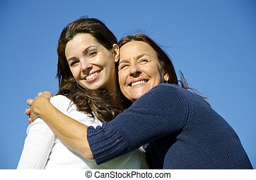 Happy mother hugging happy daughter in friendship -...