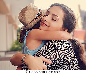 Happy mother hugging her daughter with love and natural...