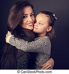 Happy mother hugging her fun daughter on dark grey background in studio with love