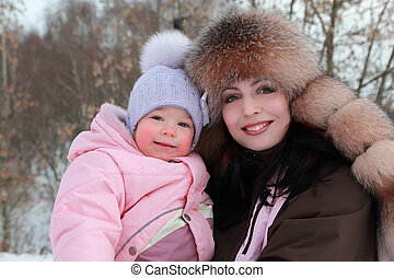 happy mother hugs her little daughter at winter, focus on woman