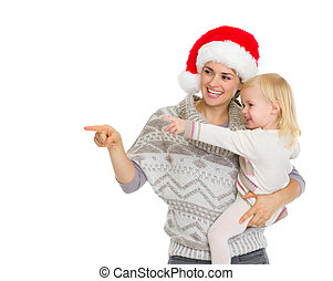 Happy mother in Christmas hat and baby girl pointing on copy space