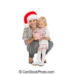 Happy mother in Christmas hat and baby girl putting coin into piggy bank