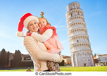 Happy mother in Christmas hat with daughter in Pisa, Italy